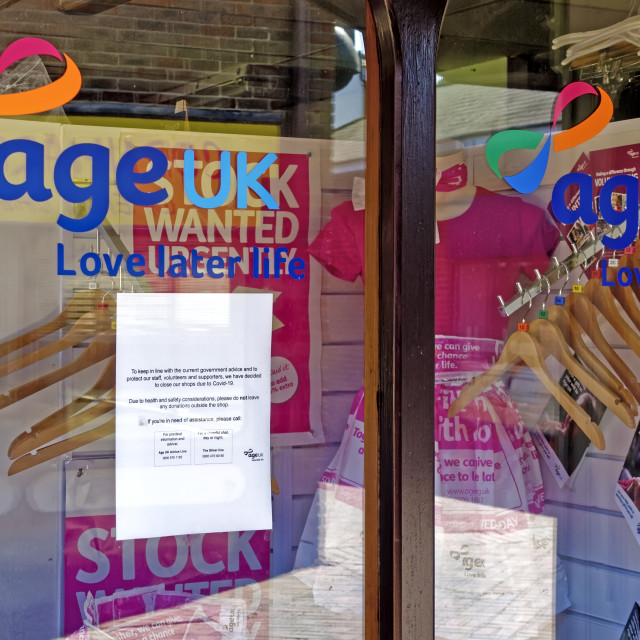 """""""A Closed due to Coronavirus sign in the window of Age UK"""" stock image"""