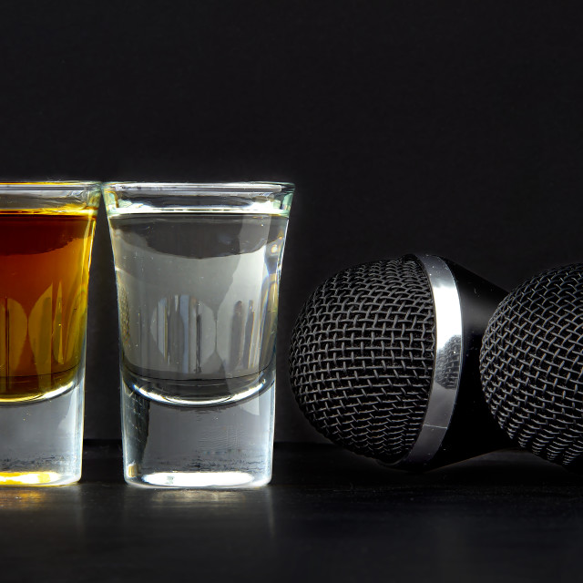 """Shoot Glasses with liquor and two karaoke microphones on a black background"" stock image"