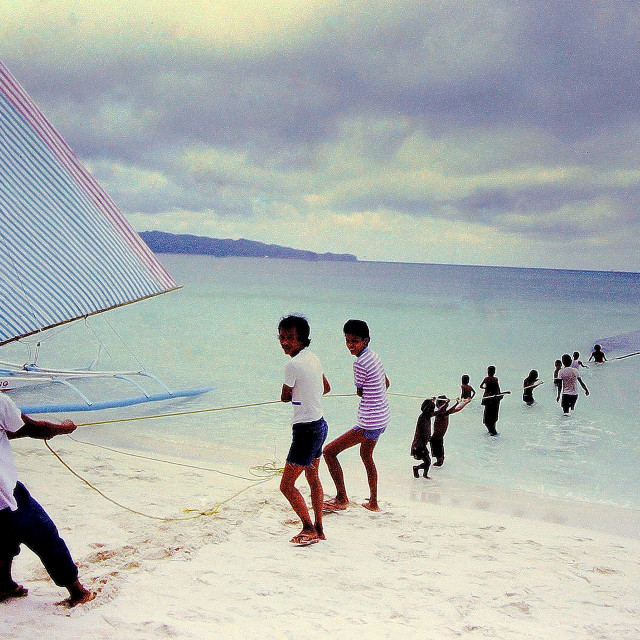 """A fishing village in the Philippines works together to pull in the day's catch in huge nets"" stock image"