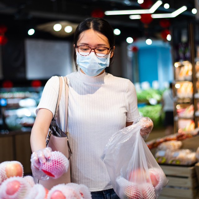 """""""Asian woman shopping for fruit in the market wearing mask and gl"""" stock image"""