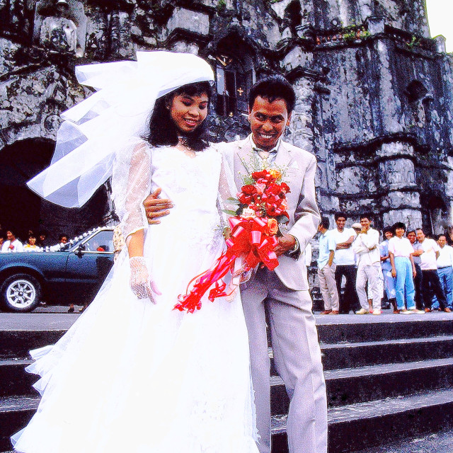 """A happy newlywed couple leaves an ancient church in the Philippines"" stock image"