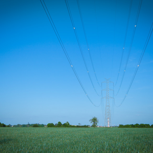 """High voltage transmission line against clear blue sky"" stock image"