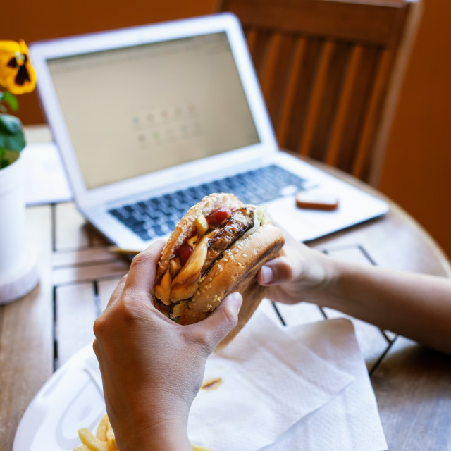 """Lunch break with cheeseburger. Smart working concept during quarantine due to..."" stock image"