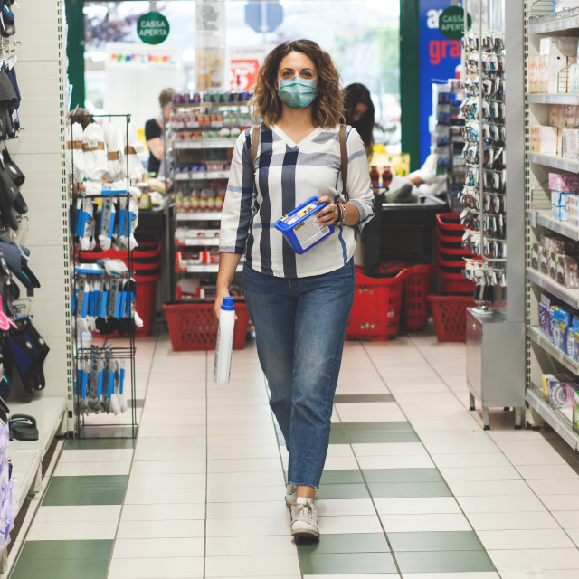 """Woman does the shopping in the supermarket wearing the surgical mask to avoid..."" stock image"