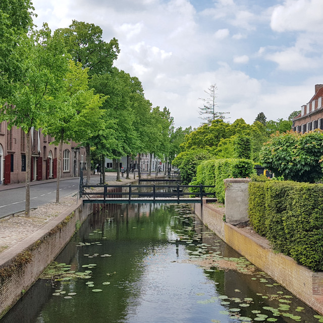 """Canal along the street and a foot bridge over the water"" stock image"