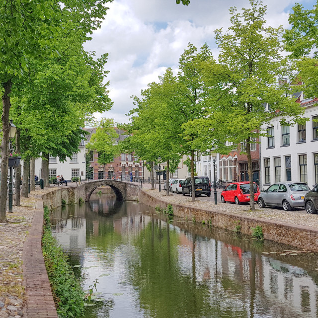 """Old cobbled street with a canal in the middle"" stock image"