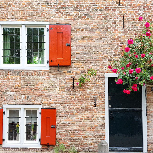 """Old brick house with windows with red shutters"" stock image"