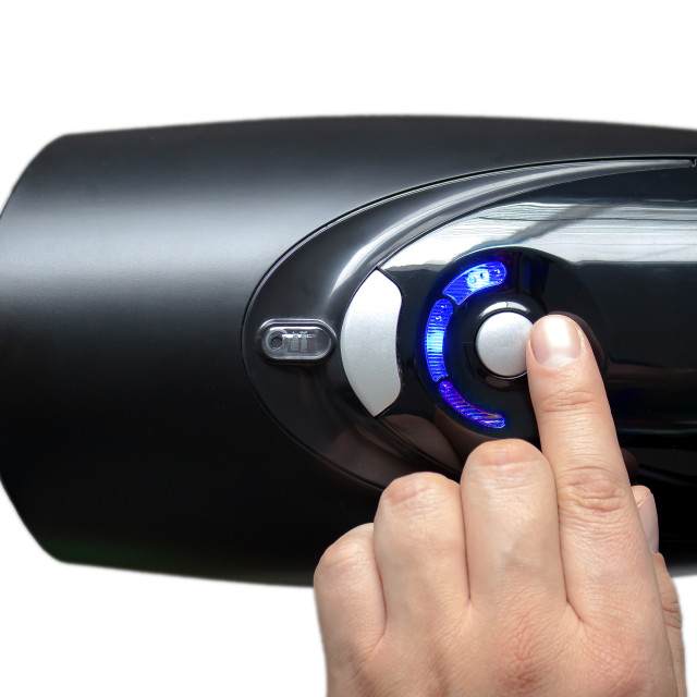 """""""An person turning on an electric air purifier on a white background"""" stock image"""
