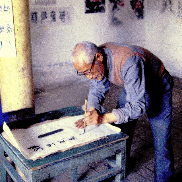 """An elderly Chinese calligraphy writer uses special brushes to make his handwriting as beautiful as possible."" stock image"