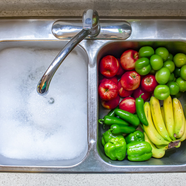 """Washing vegetables and fruits on a sing with running water and soap"" stock image"