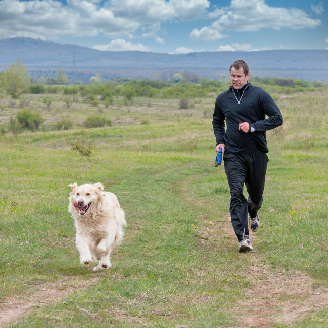 """""""Young man running with your golden retriever dog on the meadow"""" stock image"""