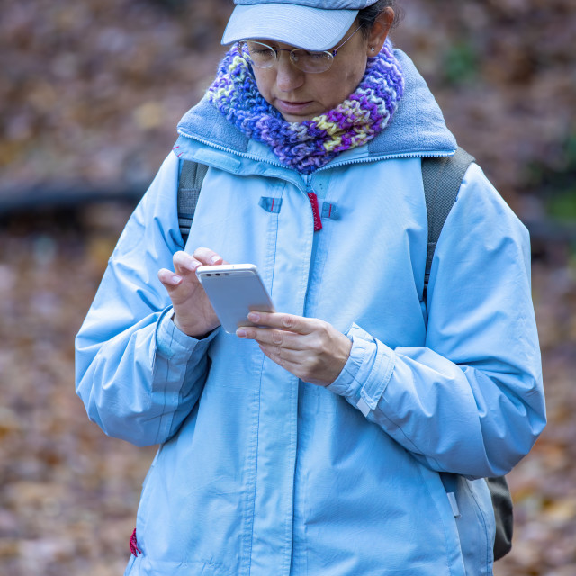"""""""Pretty tourist in the forest looking at mobile phone"""" stock image"""