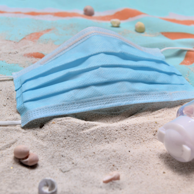 """""""close to blue surgical mask and hand sanitizer on the beach - concept vacation with covid-19"""" stock image"""