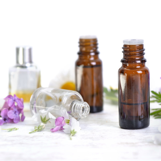 """""""bottles of essential oil and colorful petals of flowers on white table"""" stock image"""