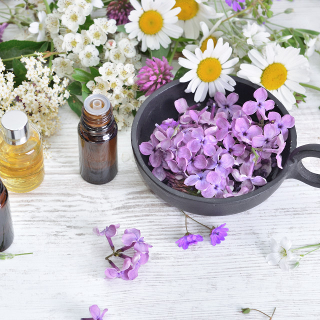 """""""bottles of essential oil and colorful petals of freshness flowers on white table"""" stock image"""