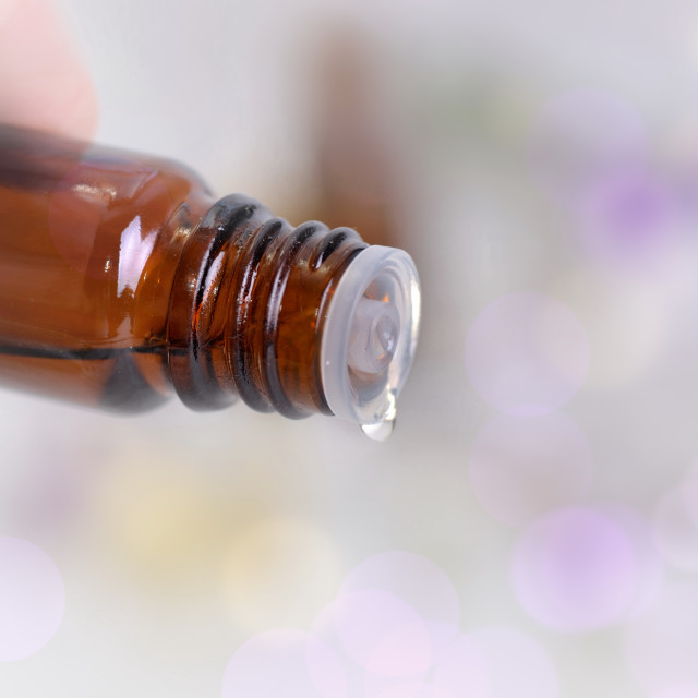 """""""close on a essential oil bottle pouring of oil on blury background"""" stock image"""
