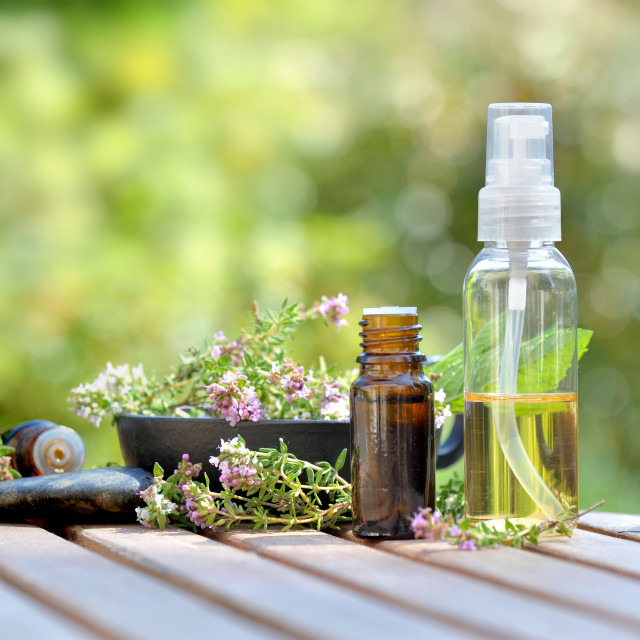 """""""bottles of essential oil and flowers of aromatic herb on atable and on green background"""" stock image"""