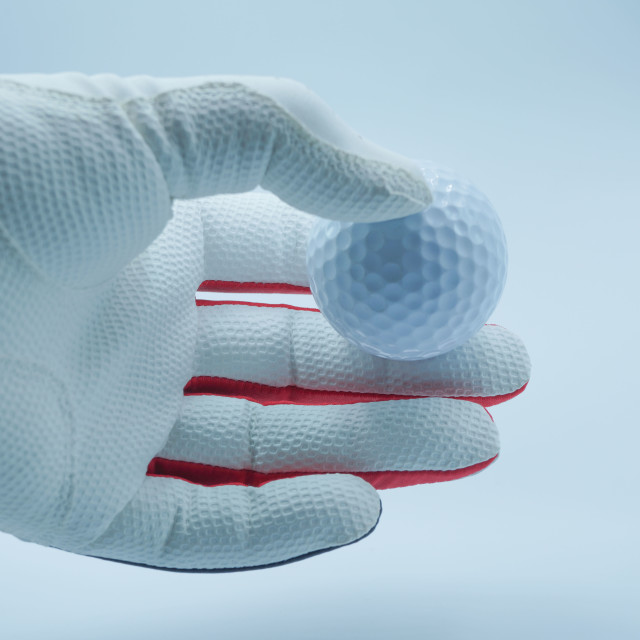 """""""White glove hands are holding a golf ball with a white backgroun"""" stock image"""