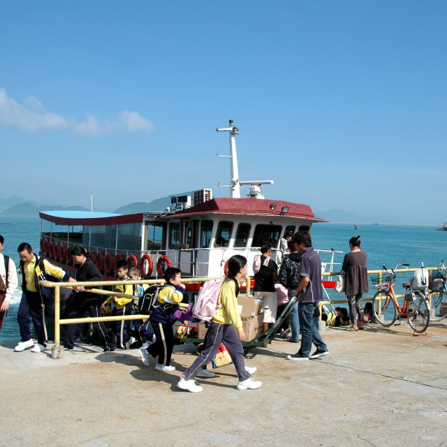 """Young school children exit their small ferry to attend school on Lantau Island, Hong Kong."" stock image"