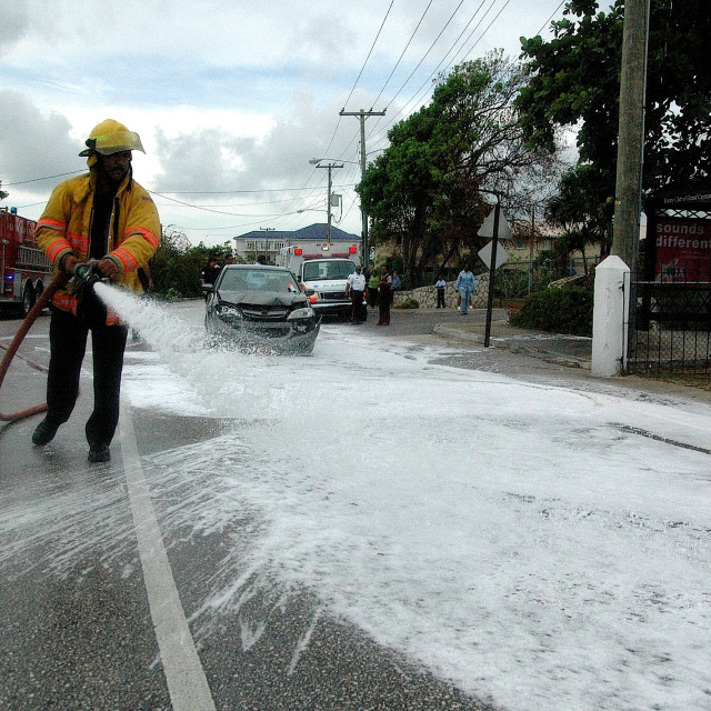 """A fireman sprays fire suppressant on a road, following a traffic accident"" stock image"
