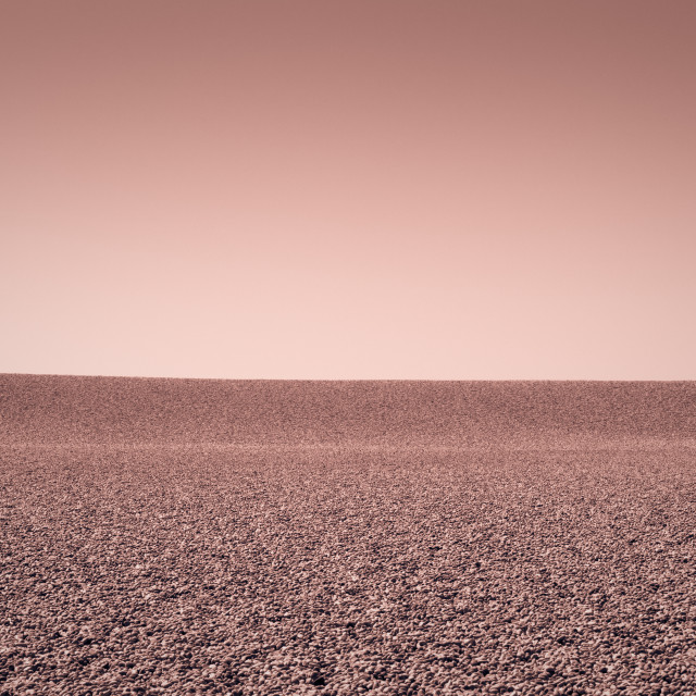 """""""Red tinted image of pebbles against a clear sky"""" stock image"""