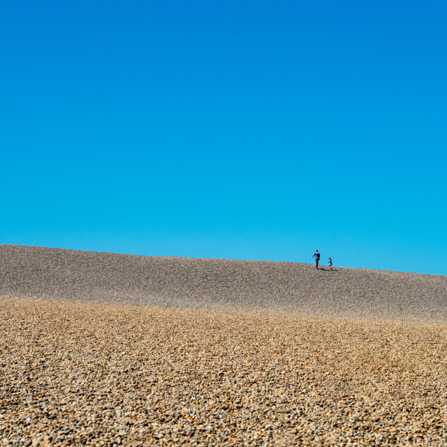 """""""Two people walking up Chesil beach, an 18 mile long pebble and shingle tombolo connecting the Isle of Portland to mainland England, Dorset, UK. Chesil beach is a popular landscape attraction in the south west of England, connecting the Isle of Portland to"""" stock image"""