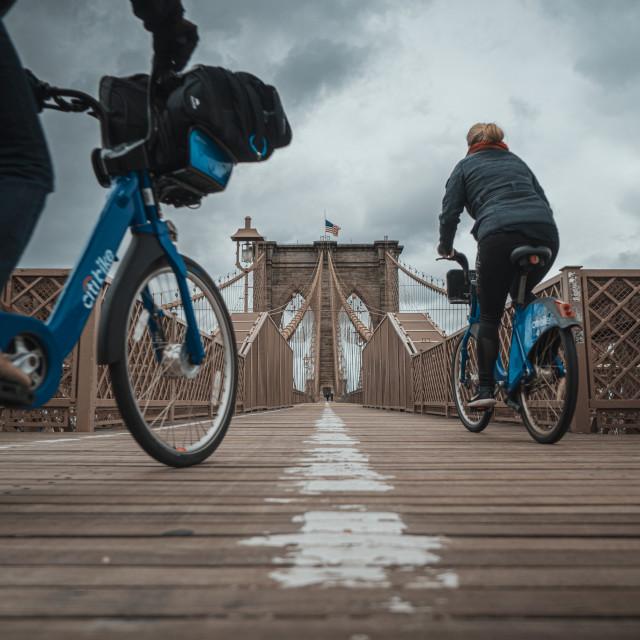 """""""Biking across the Brooklyn Bridge"""" stock image"""
