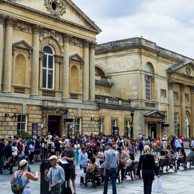 """""""People queueing to visit and sitting outisde the Roman Baths, Bath, Somerset, England, UK."""" stock image"""