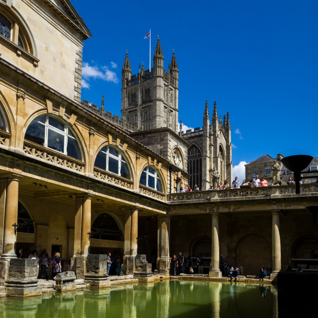 """""""Visitors exploring the historic Roman Baths with Bath Abbey towering above, Bath, Somerset, England, UK. The Great Bath is the largest pool in the Roman Baths, a well preserved and historical site from Roman times built around 70 AD. It is thought the Rom"""" stock image"""