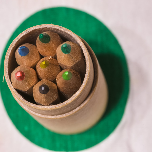 """""""Colored pencils inserted in a cardboard cylinder on a colored pl"""" stock image"""