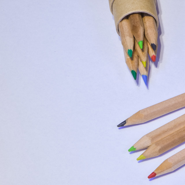 """Colored pencils resting on white sheet, horizontal image"" stock image"