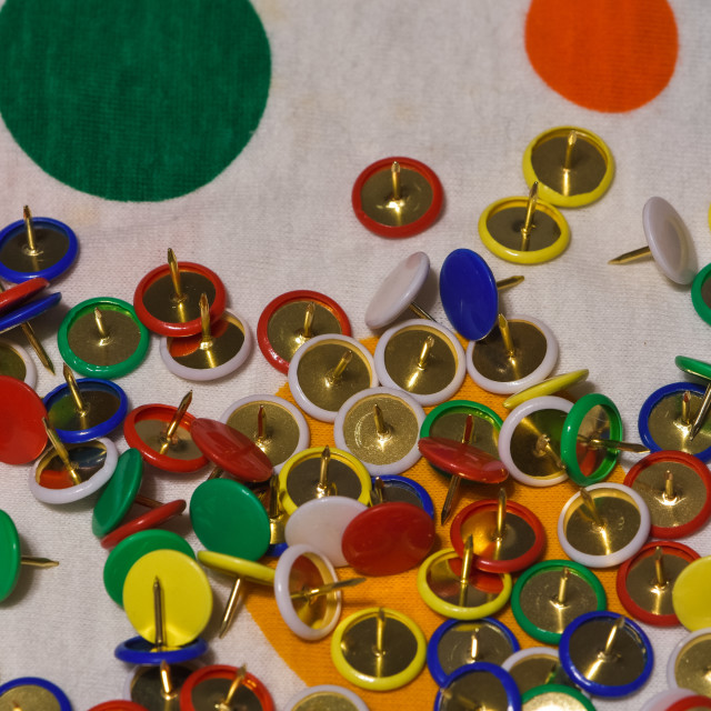 """""""Scattered thumbtacks on a colored plane"""" stock image"""
