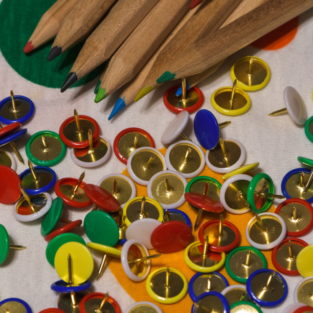 """""""Thumbtacks and colored pencils scattered on a colored plane"""" stock image"""