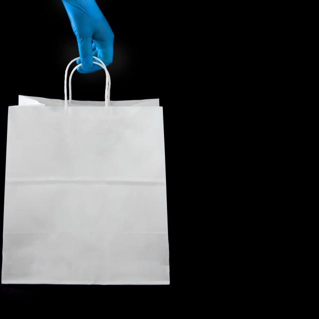"""A person wearing protective latex gloves holding a shopping paper bag"" stock image"