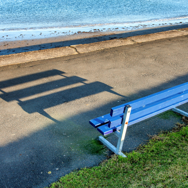 """""""Seat on a promenade casting a shadow on a sunny day"""" stock image"""