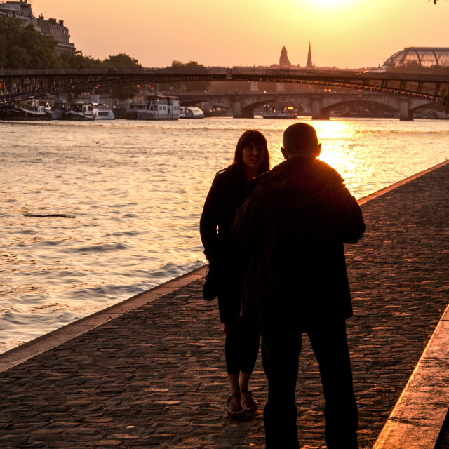 """Couple Walking by the River Seine, Paris at Sunset."" stock image"