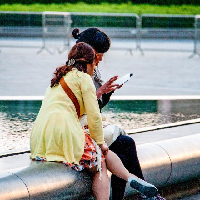 """""""Girls Checking Tourist Information, Paris."""" stock image"""