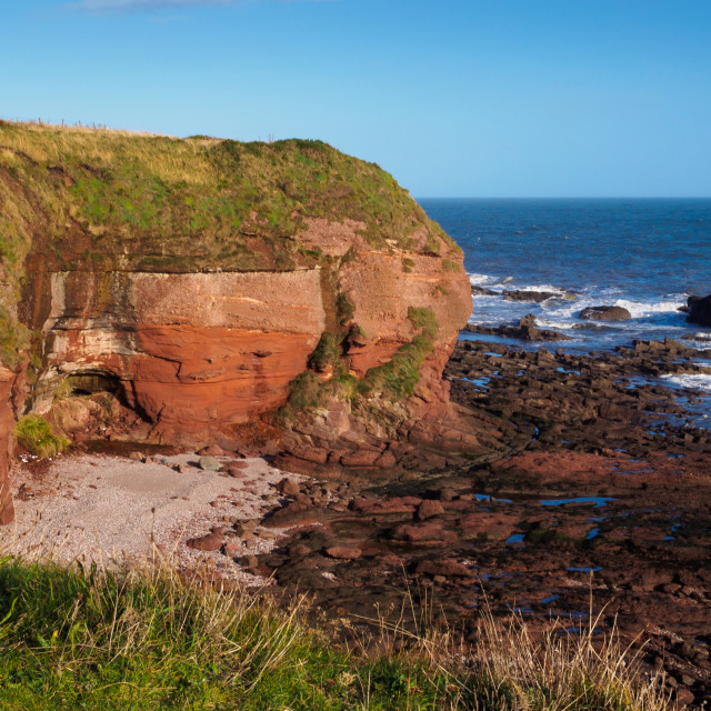 """""""Steep rock face and secluded rock beach at Seaton Cliffs - Arbro"""" stock image"""
