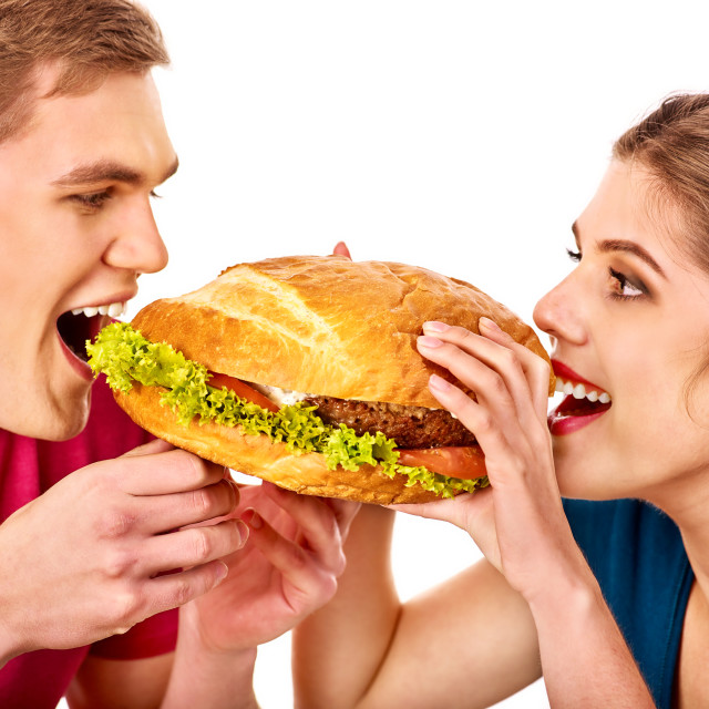 """Couple eat fast food on hamburger eating competition"" stock image"