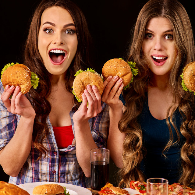 """Group women eat best hamburger and pizza in burger bar"" stock image"