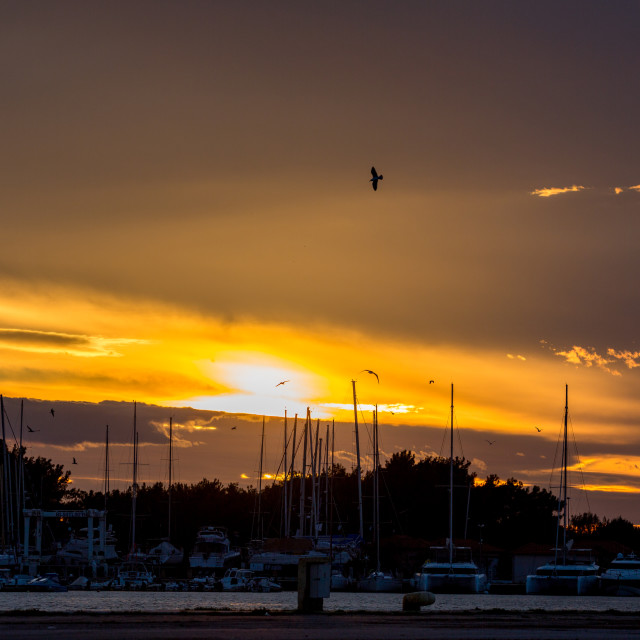 """Orange golden sunset over port of Porto Lagos"" stock image"