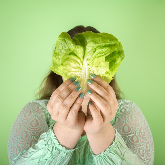 """""""Dieting concept with a chubby woman holding a salad leaf"""" stock image"""