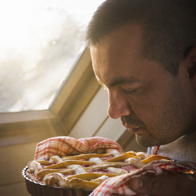 """""""Young man smelling raspberry pie held in hands"""" stock image"""