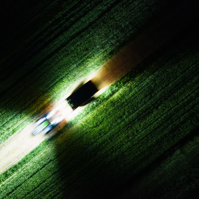 """""""Abstract top down image of farmland and driving tractor at night"""" stock image"""