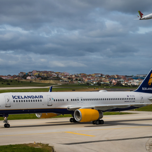 """Boeing 757 passenger aircraft of Icelandair taxying under a cloudy sky"" stock image"