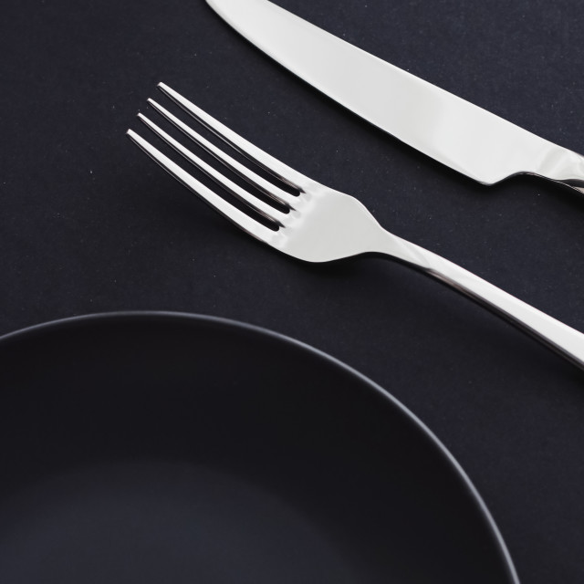 """Empty plates and silverware on black background, premium tableware for..."" stock image"