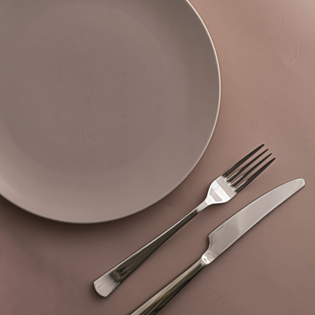 """Empty plate and cutlery as mockup set on brown background, top tableware for..."" stock image"