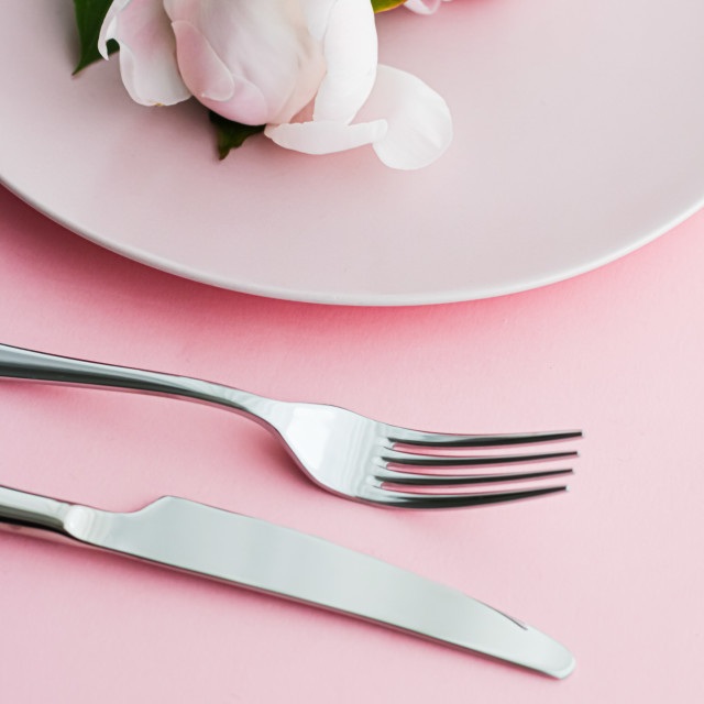 """Dining plate and cutlery with peony flowers as wedding decor set on pink..."" stock image"