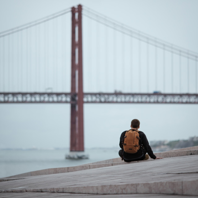 """""""Young man sitting on a hill looking at beautiful bridge"""" stock image"""