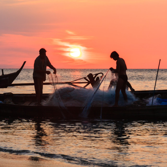 """""""Two fishermen sorting nets on their boat"""" stock image"""